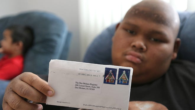 Justin Chey, a 13-year-old who is battling a brain tumor, holds an envelope that was sent to The Des Moines Register from an anonymous donor who read about Justin's battle. The envelope contained $1,000.