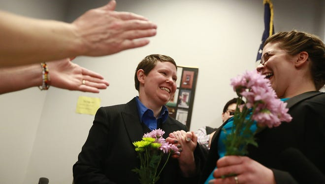 Jennifer and Alexi Chapin-Smith were married at the Washtenaw County Clerk's Office in Ann Arbor, Mich., on Saturday, March 22, 2014. About 100 couples are uncertain of the status of their marriages after a temporary stay of a lower court ruling that declared Michigan's ban on same-sex marriage as unconstitutional.