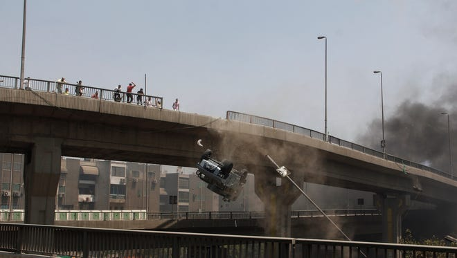 Protesters push a police vehicle off a bridge in Cairo. Security forces cleared sit-in camps of supporters of ousted leader Mohammed Morsi on Wednesday.