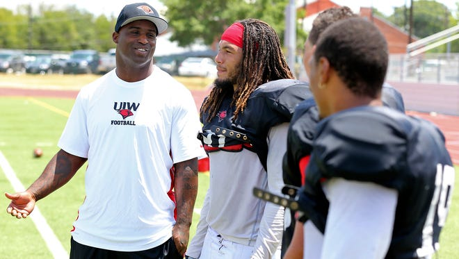 University of the Incarnate Word new assistant football coach Ricky Williams, left, talks with players during an NCAA college football practice on Aug. 15.