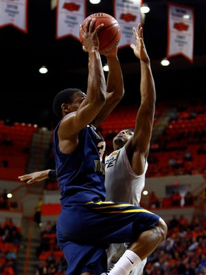 """West Virginia guard Juwan Staten takes it up against Oklahoma State guard Anthony Hickey Jr. The 10-team Big 12 plays a full round-robin schedule. """"You can play a double round-robin and if you didn't have good teams in your league, it could hurt you,"""" Mountaineers coach Bob Huggins says. """"What really helps us is there's (six) teams ranked in the Top 25 and seven teams in the top (41) in the RPI."""""""