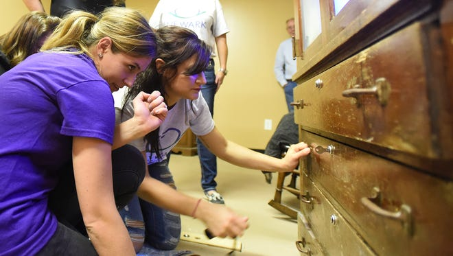 Emily Horne and Brittany Beavers search for what a small key unlocks in the grandma's attic themed escape room at Escape It in Newark. The two co-workers were part of a team from Newark Smiles Family Dentistry who attempted to solve puzzles and find clues in under 45 minutes to find a hidden treasure.