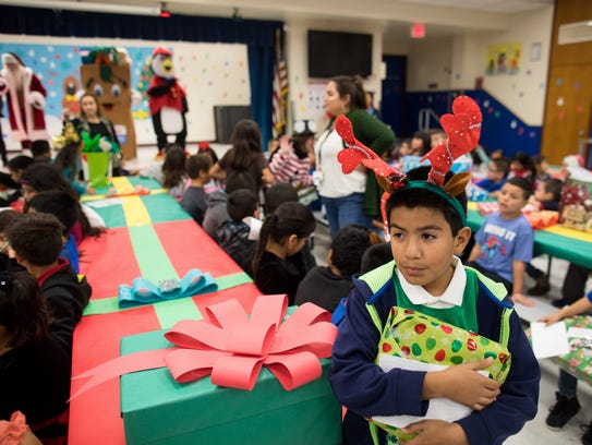 Alex Ortiz holds a present as he waits to open it during Crockett Elementary's second annual Christmas Tree Angel event on Wednesday, Dec. 13, 2017.