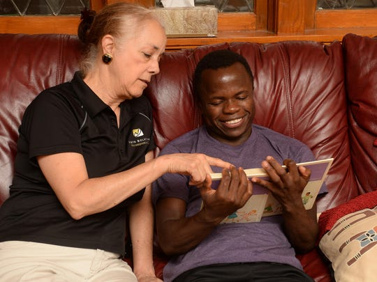 Guy Seguele practices reading at home with his foster mother Linda Vomaske on Thursday, Sept. 15, 2016. Seguele survived a civil war in Africa and is a First Class scholar.