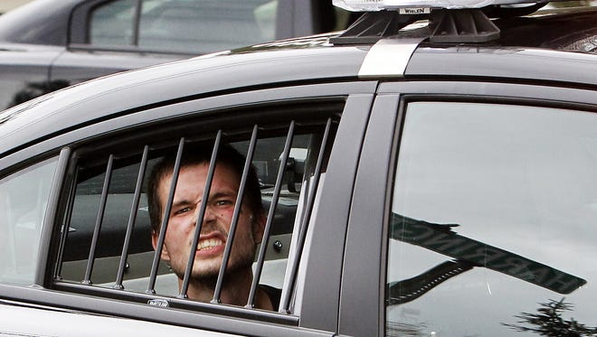 Burglar Zachary Johnson acts out in the backseat of a police car on Sept. 18, 2015, minutes after he was arrested following a three-hour manhunt.