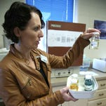 Eva Maydole, a Water Quality Specialist at the Great Falls Water Treatment Plant explains collected water treatment results. Based on the test results, a water sample can become blue, green, or orange. A clean result is always a light yellow color.