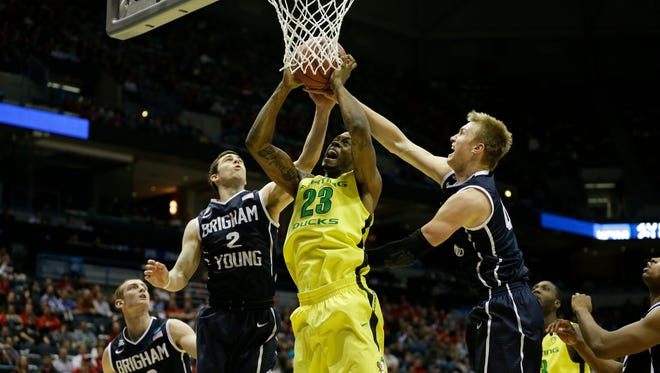 Oregon forward Elgin Cook (23) goes up for a layup, guarded by Brigham Young guard Matt Carlino (2) and forward Eric Mika (00) during the second round of the 2014 NCAA Tournament at BMO Harris Bradley Center.