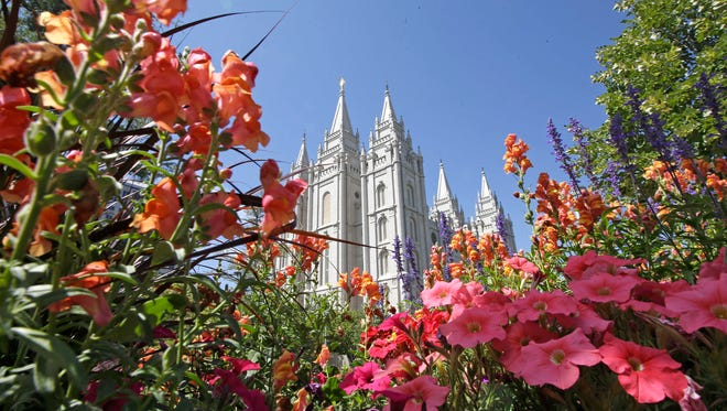 This Aug. 4, 2015, file photo, flowers bloom in front of the Salt Lake Temple, at Temple Square, in Salt Lake City. Gay and lesbian Mormons and their supporters are reeling over a rule change by church officials that says members in same-sex marriages can be kicked out, and bars their children from being baptized unless they disavow same-sex relationships.