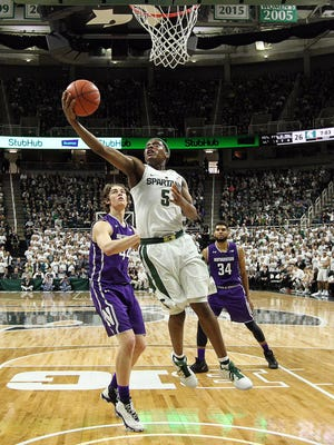 Michigan State guard Cassius Winston (5) drives to the basket against Northwestern forward Gavin Skelly (44) during the first half of MSU's 61-52 win over Northwestern Friday at Breslin Center.
