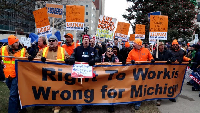 Protesters march towards the steps of the state Capitol in Lansing to protest the signing of the right-to-work bill by Gov. Rick Snyder on Tuesday, Dec 11, 2012.
