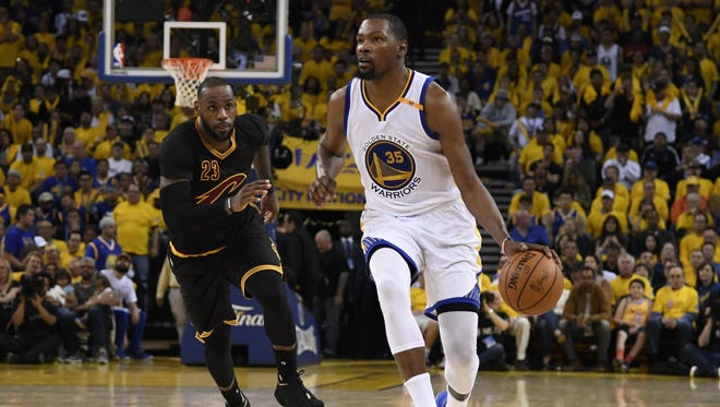 Golden State Warriors forward Kevin Durant (35) dribbles the ball past Cleveland Cavaliers forward LeBron James (23) during the second half in game two of the 2017 NBA Finals at Oracle Arena.