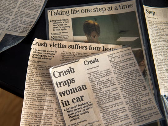 Newspaper clippings from 1998 detail the car crash and ensuing recovery that Stephanie Navratil endured, as seen in her Spring Township living room on Wednesday, Jan. 3, 2018. At age 23, Stephanie Navratil was trapped in her car for four hours after crashing on her way home from work early New Year's Day in 1998. Suffering injuries to her jaw, pelvis and legs, Navratil underwent multiple surgeries and extensive therapy that have enabled her to pursue a full life with her family and three children.