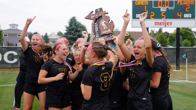 Lansing Christian players celebrate their state championship following a win over Kalamazoo Christian, Saturday, June 17, 2017, in Williamston.