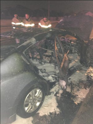 Firefighters work to extinguish a vehicle fire just after midnight Thursday morning.