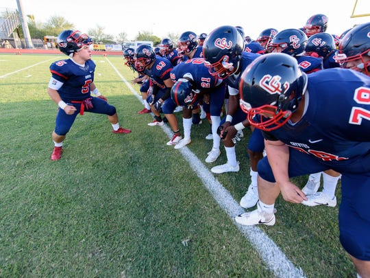 Centennial's Alex Escobar(C) (#5) gets his team warmed up before they take the field for their high school football game against Pinnacle on Thursday, Sept. 14, 2017, at Centennial High School in Peoria, Ariz.