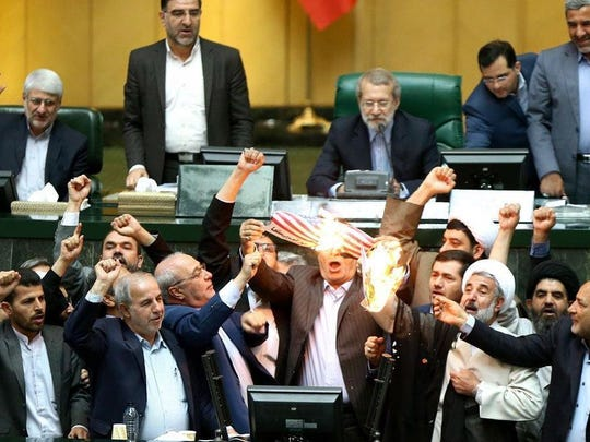 A handout picture made available by the Iranian parliament office shows Iranian lawmakers burn a U.S. flag during the parliament session in Tehran.