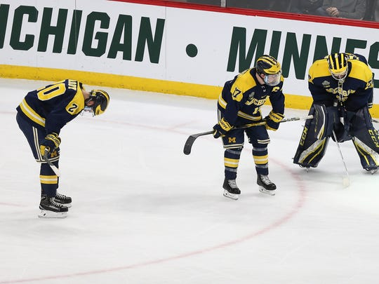Michigan's Cooper Marody (20), Tony Calderone (17) and Hayden Lavigne (30) react to a 4-3 loss to Notre Dame in a semifinal in the NCAA men's Frozen Four college hockey tournament Thursday, April 5, 2018, in St. Paul, Minn.