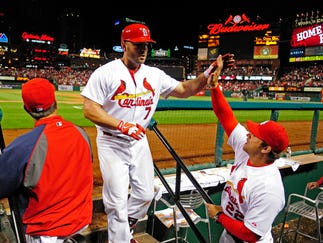 Apr 28, 2014; St. Louis, MO, USA; St. Louis Cardinals left fielder Matt Holliday (7) high fives manager Mike Matheny (22) after hitting a solo home run off of Milwaukee Brewers starting pitcher Yovani Gallardo (not pictured) during the sixth inning at Busch Stadium. Mandatory Credit: Jeff Curry-USA TODAY Sports