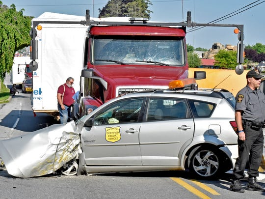 Emergency personnel work at the scene where an escort car, front, that was leading on oversized load, was struck by a passing vehicle that collided with a school bus in East Lampeter Township, Pa., May 17, 2017. Authorities say the school bus flipped on its side in a hit-and-run accident in eastern Pennsylvania, sending more than a dozen people to the hospital, including two students with trauma injuries. Police were seeking a light-colored sedan involved in the crash that sped away. (Blaine Shahan/LNP via AP)
