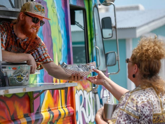 Caleb Cunningham hands Tarra Sherer, of Battlefield, her order at Nat'cho Ordinary Taco during the Food Truck Showdown at Battlefield Mall on July 8, 2017. These days, the food truck can be found in Bolivar.