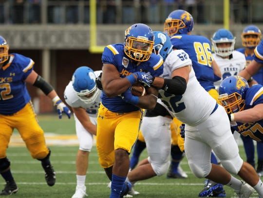 SDSU's Mikey Daniel tries to fight off a tackle from