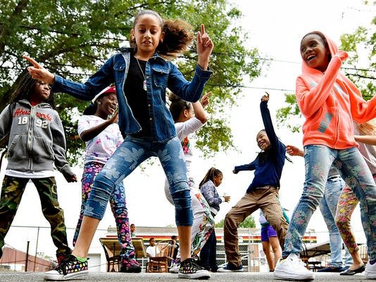 Sanicia Castro, 8,front left, of Seven Valleys, and Dymond Gonzalez, 8, front right, of York City, in back from left, Najeim Johnson, 10, and Najah Johnson, 10, and Aquajadai Williams, 11, center, all of York City, dance with others in the street as music plays during Mardi Gras Noir Picnic Cook Off & Chopped Competition block party at G's Jook Joint Restaurant & Lounge in York, Pa. on Saturday, Sept. 26, 2015. Dawn J. Sagert - dsagert@yorkdispatch.com