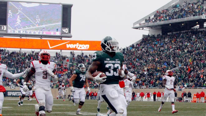Michigan State's Jeremy Langford (33) scores a touchdown on a 38-yard run in front of Rutgers' Delon Stephenson (27) and Steve Longa (3) during the second quarter of MSU's win Saturday in East Lansing.