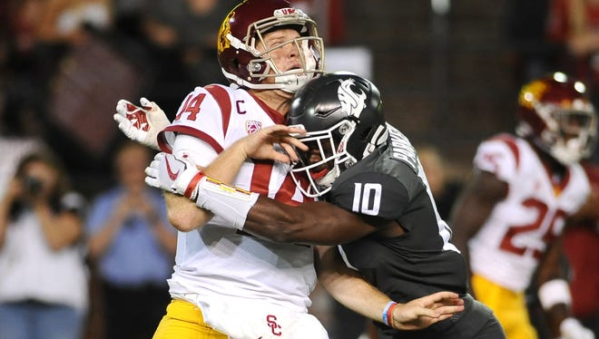 Sep 29, 2017; Pullman, WA, USA; USC quarterback Sam Darnold (14) is hit after a throw by Washington State defensive back Kirkland Parker (10) during the second half at Martin Stadium. The Cougars won 30-27.