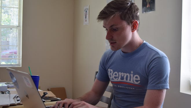 "Neil C. Spencer, organizer with Noles Want Bernie, works at a desk in the group's ""headquarters,"" a house on Dellview Drive on loan from a Sanders supporter."