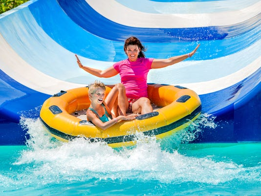 Child with mother on water slide at aquapark