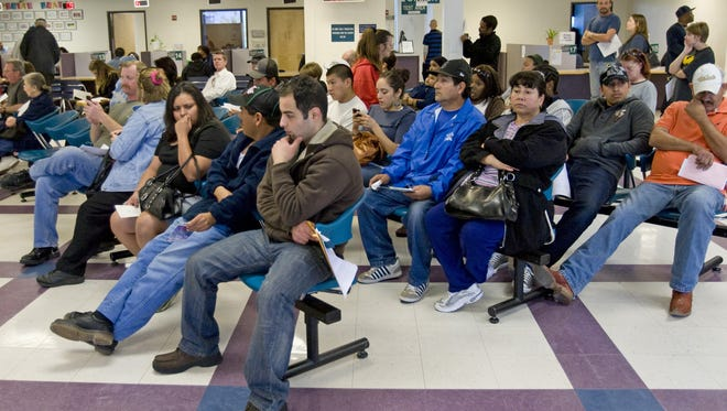 Customers wait at the MVD Central Phoenix branch for service.  This branch, which served more than 11, 000 customers a month, was one of the 11 MVD offices that closed in 2010.