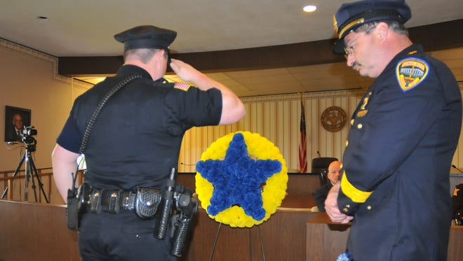 An officer salutes after placing a flower to honor a fallen law enforcement officer during the 2015 law enforcement memorial service.