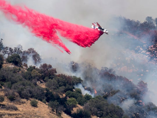 CALFIRE and Tulare County Fire departments work a wildland fire on Wednesday, June 7, 2017 above Three Rivers along Dinely Drive.