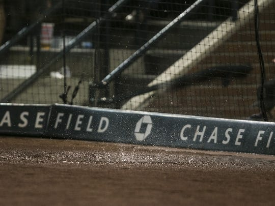 A puddle forms behind home plate after rain finds its way through a leak in the roof during a game against the Giants at Chase Field in Phoenix on Friday, July 17, 2015.