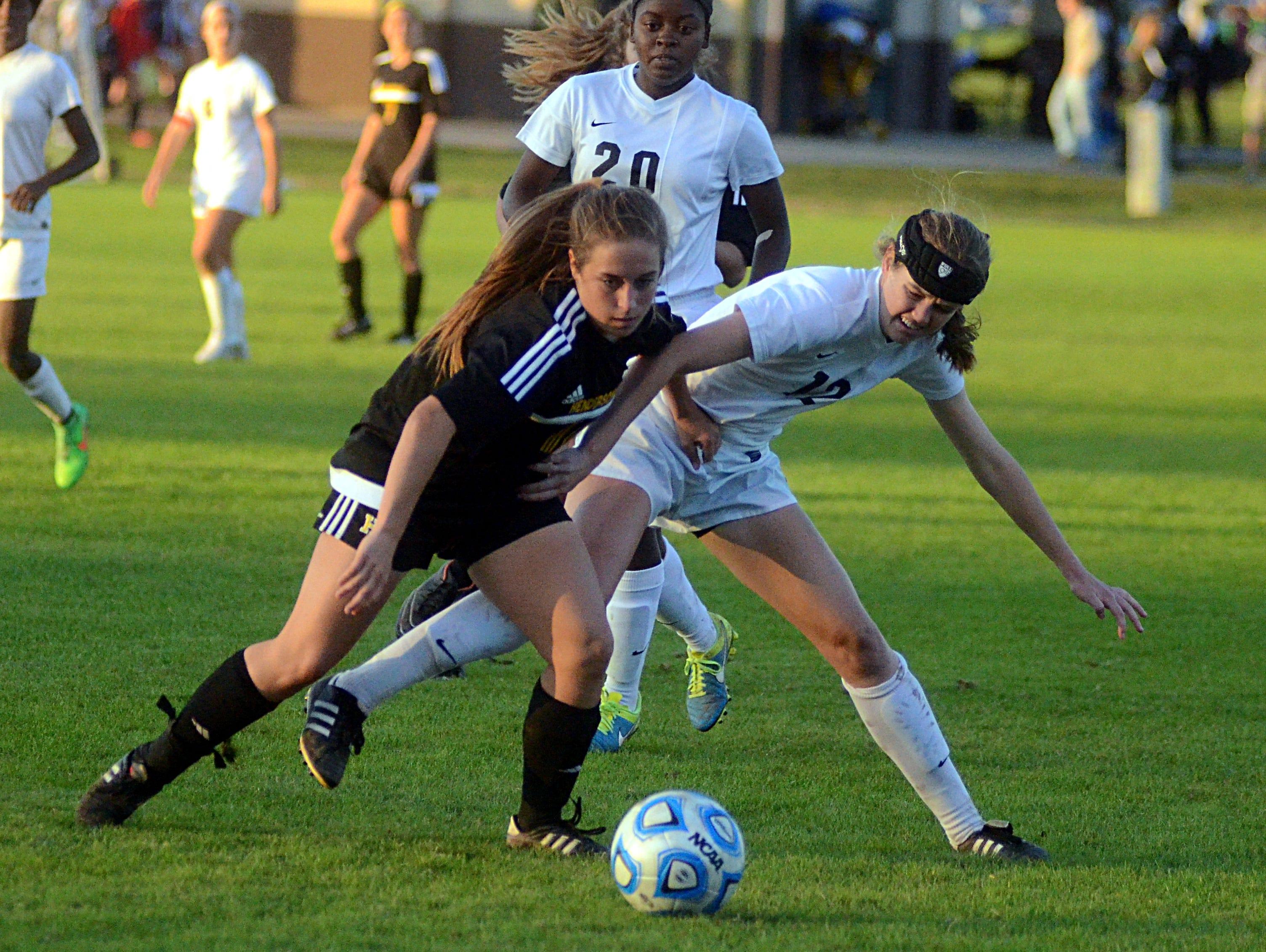 Hendersonville High senior Maddie Kimler battles Houston junior Katrina Ostrom for possession during second-half action.