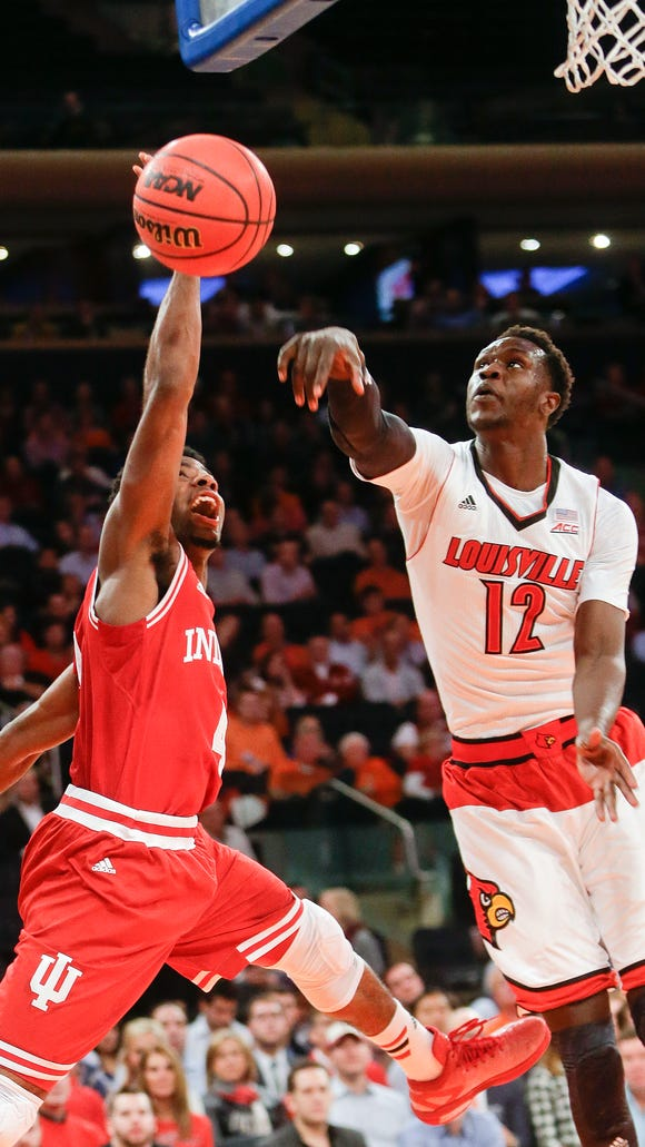 Louisville's Mangok Mathiang (12) blocks a shot by Indiana's Robert Johnson (4) during the first half of an NCAA college basketball game Tuesday, Dec. 9, 2014, in New York. (AP Photo/Frank Franklin II)