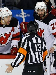 New Jersey Devils' Taylor Hall (9) and Kyle Palmieri (21) talk to a referee against the Winnipeg Jets during the third period of an NHL hockey game in Winnipeg, Manitoba, Saturday, Nov. 18, 2017. The Jets defeated the Devils 5-2. (John Woods/The Canadian Press via AP)