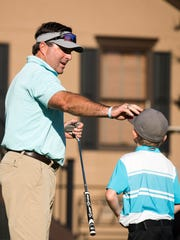 Todd Merriss fixes his son Jackson's cap after he practiced his putting at the Smithfields Country Club on Wednesday, Oct. 5, 2017.