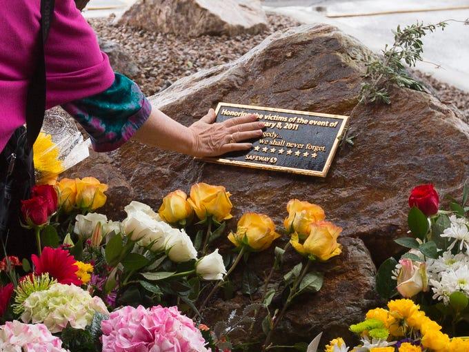 Tucson resident Valerie Miller touches a memorial plaque