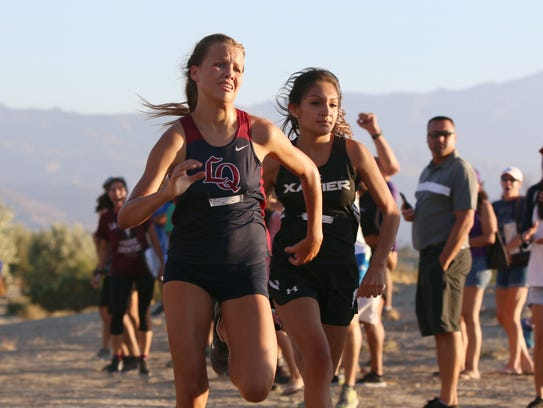 Varsity runners race to the finish during the first