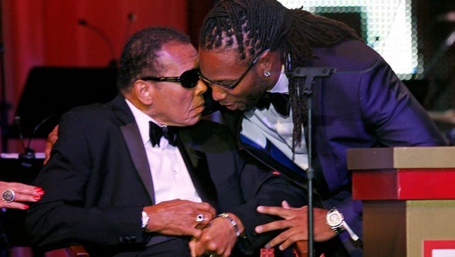 Muhammad Ali is greeted by the Arizona Cardinals' Larry Fitzgerald during the Celebrity Fight Night event in 2012.
