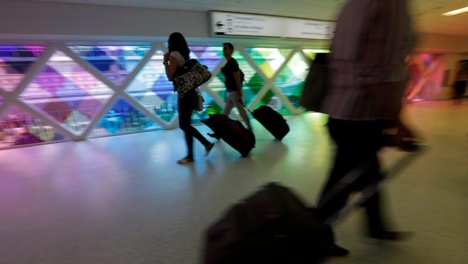 Passengers travel through Miami's airport on Sept. 27, 2012.
