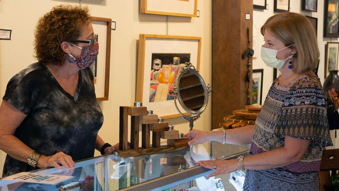 Art Mob owner Michele Sparks, left, talks to Elizabeth Peck of Arden early Saturday afternoon, less than a day after Gov. Roy Cooper's order making it mandatory for people to wear masks while in public took effect. Sparks said she already has had excellent compliance from customers who have entered her gallery since early May.