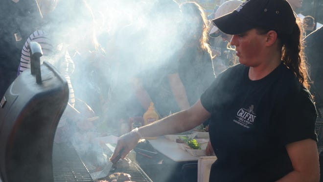 Talija Wood from Griffin Grill and Pub was woking in the smoke while cooking hamburgers.