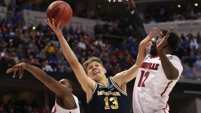 Michigan Wolverines forward Moe Wagner scores against Louisville forward Mangok Mathiang during the second half of U-M's 73-69 win Sunday, March 19 at Bankers Life Fieldhouse in Indianapolis in the second round of the 2017 NCAA tournament.