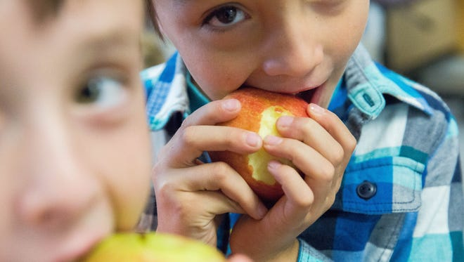 Joel Nuñez, 6, center, and Aaron Ramirez, 7,  left,  both first grade students at Valley View Elementary, take bites of Braeburn apples during Apple Crunch Week. Tuesday October 24, 2017. Teachers and students  through out Las Cruces Public Schools will be trying different types of apples every day this week. This program is intended to help students eat healthier, and was funded through the SNAP-Ed  grant from the United State Department of Agriculture.
