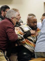 James Whitlow, brother of murder victim Derrick Whitlow, is restrained after lunging at Mastella Jackson during her sentencing Thursday at the Outagamie County Justice Center.