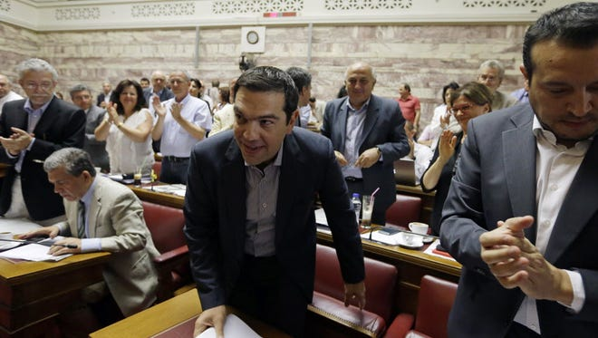 Greek Prime Minister Alexis Tsipras arrives for a meeting as lawmakers with the Syriza party applaud him at the Greek Parliament in Athens on July 10, 2015.