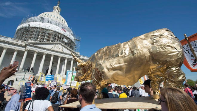 Protesters carry a replica of the Wall Street Bull on Capitol Hills in April 2016.