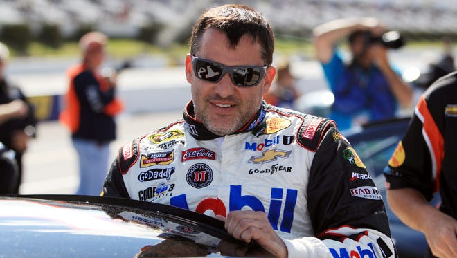 Tony Stewart (14) climbs into his car during qualifying in June for the Pocono 400 at Pocono Raceway.
